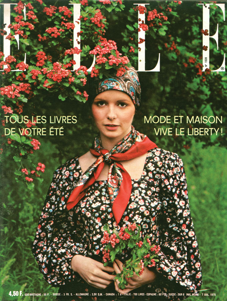 1975 Elle France magazine cover featuring a model wearing a Liberty botanical-print head scarf, neck scarf and dress, standing by a flowering shrub and holding a small bouquet of red flowers.