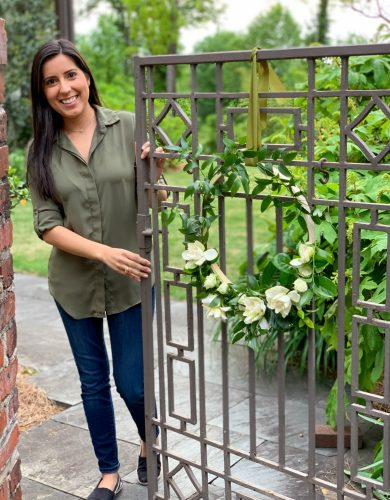 Jessica Cohen stands at a wrought iron gate decorated with a floral hoop of gardenias, spray roses, and Italian ruscus