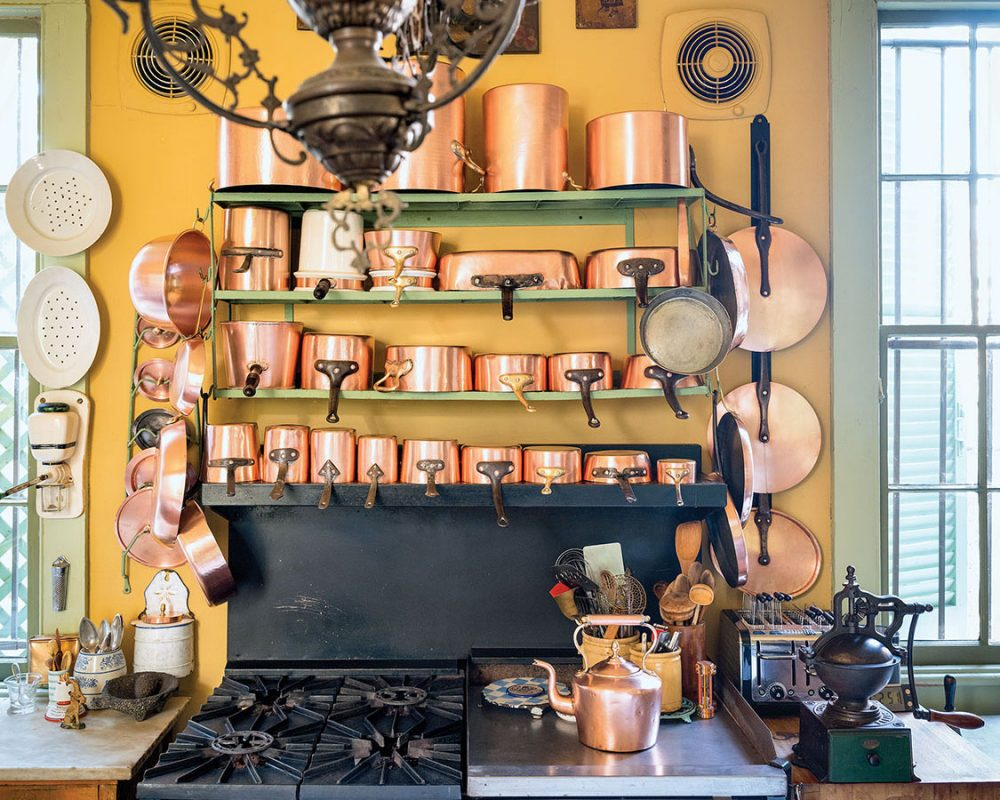 4-tier rack of copper pots above a black chef's stove with gas burners and griddle, in a Patrick Dunne's New Orleans home kitchen