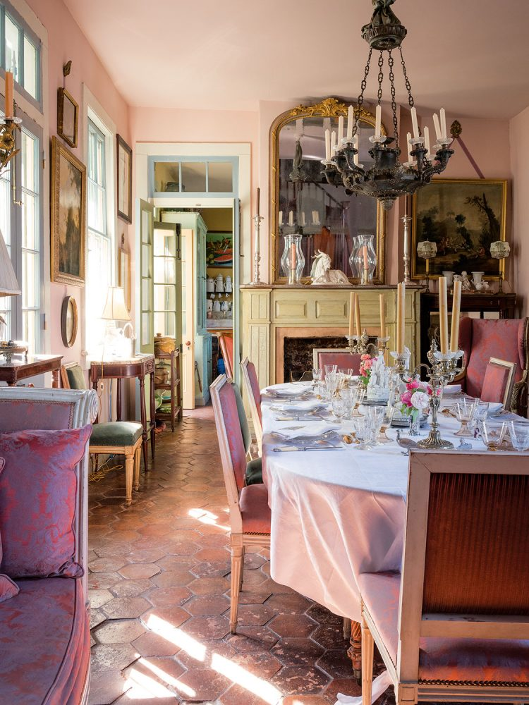 A cozy, elegant New Orleans dining room with pail pink walls and ceiling, aqua wood trim, and hexagonal rust-colored tile floor. The room is filled with antiques including a large, intricate mirror over the mantel and many paintings.