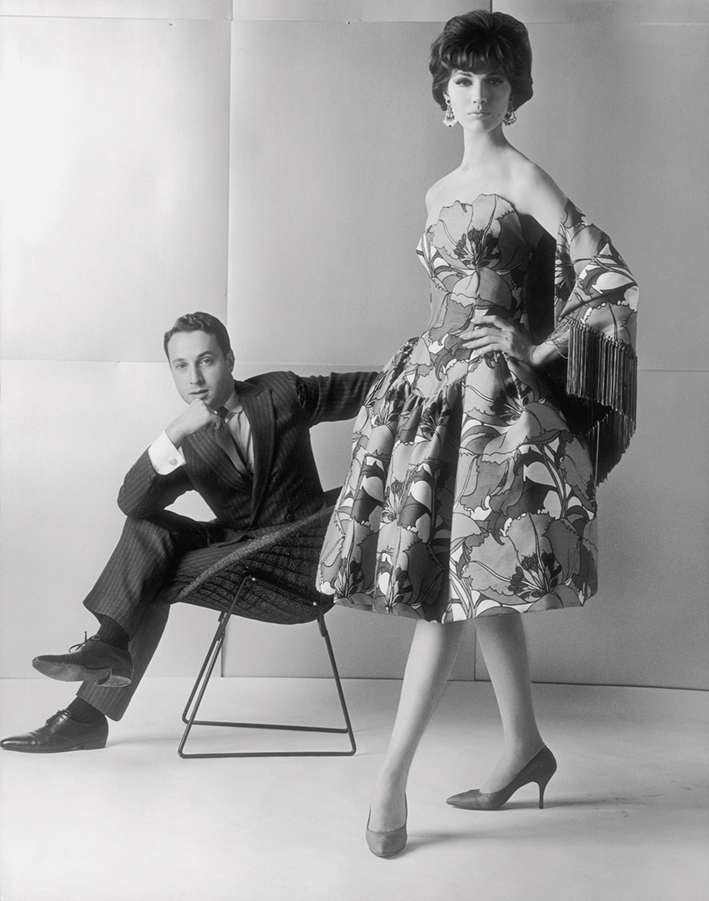 Black-and-white photo of designer Arnold Scaasi in a pin-stripe suit sits in a chair in the background. In the foreground, a model wears a sleeveless floral dress and fringed shawl