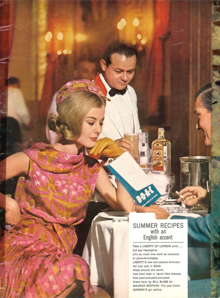 Vintage Gordon's Gin ad featuring model in a 1960s-style pink and gold Liberty botanical-print dress and hat, a fine-dining establishment with a date. A waiter in a white jacket is serving them a cocktail.