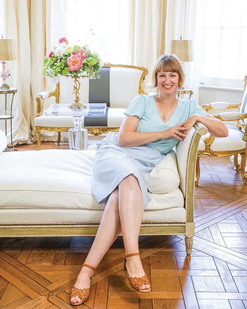 Destiny Pinson, wearing a pale blue shirt and skirt, sits in on a chaise in a light and bright room in a New Orleans home