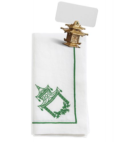 A gold-colored, pagoda-shaped place holder, and a white napkin with green embroidered border and green embroidered pagoda motif in the corner