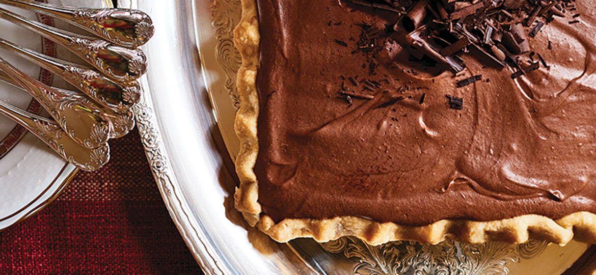 A chocolate dessert tart on a silver platter from The Art of the Host by Alex Hitz