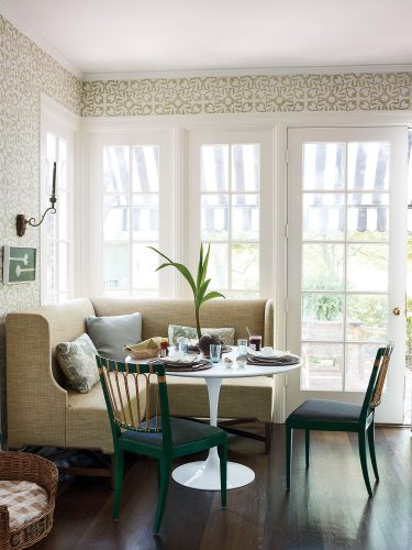A light and airy breakfast room designed by Tom Scheerer with an upholstered corner banquet, a modern round table with white pedestal base, and two chairs. French doors and mullioned windows.