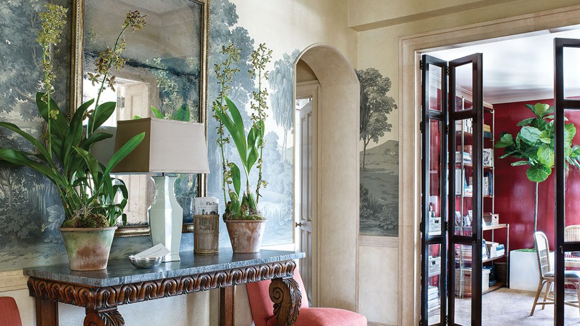 A scene from the pages of Tom Scheerer: More Decorating: An entry area features wallpaper with a large monotone landscape scene and an understated crystal chandelier. Two coral slipcovered armless chairs flank a long narrow table that sits flush against the wall, topped with a large square mirror. A large basket is beneath.