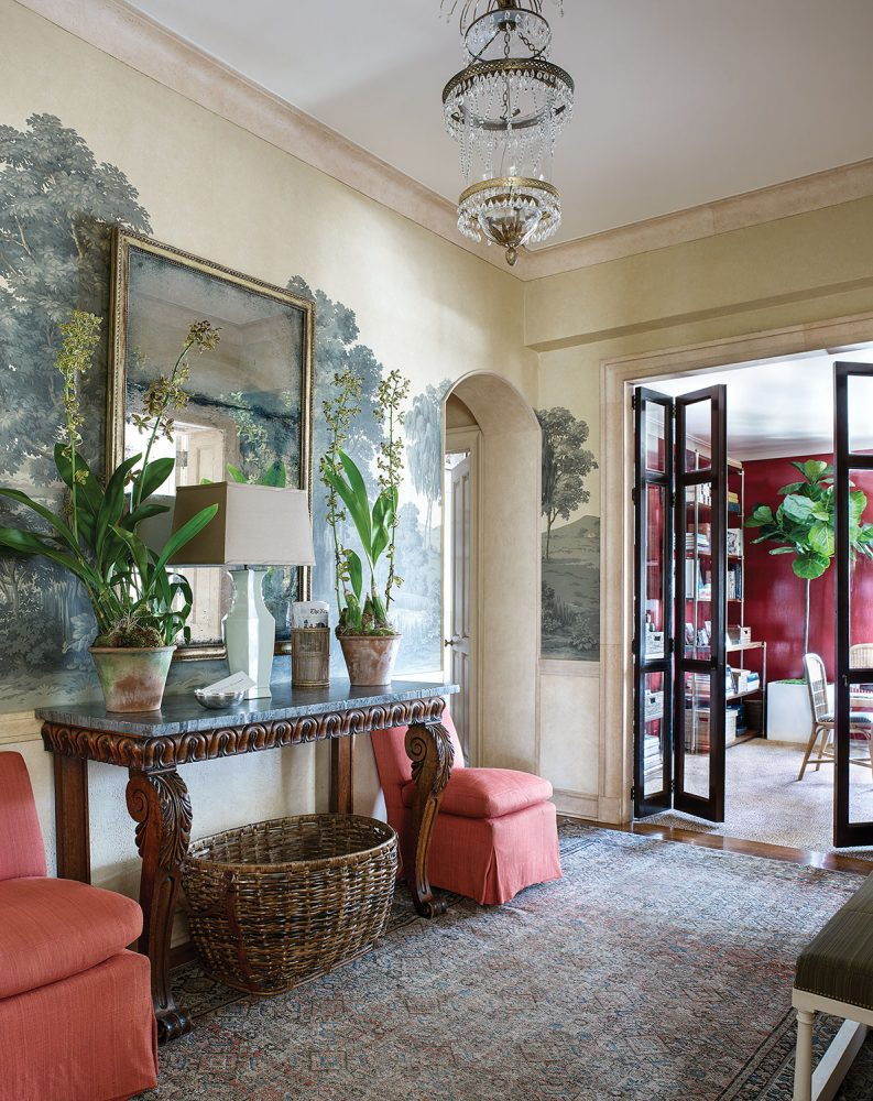 The room also features an understated crystal chandelier and--between the coral slipper chairs--a long narrow carved wood table with marble top, which sits flush against the wall and is topped with a large square mirror with a gilt frame. A large basket is beneath.