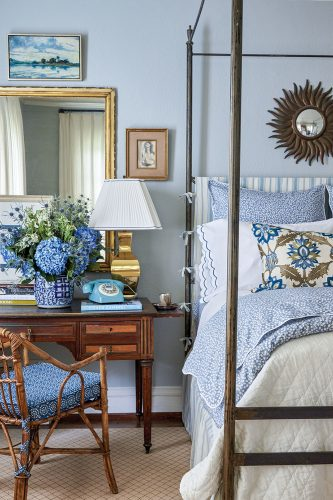 A desk and chair beside a four-poster bed is decorated with a large arrangement of hydrangeas, a vintage-inspired blue phone with rotary dial, a brass lamp, and large rectangular mirror with a brass frame. Setting off the blue-and-white decor are walls are painted a pale blue.