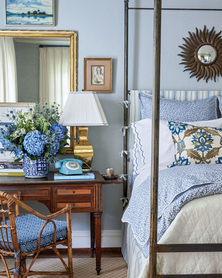 A desk and chair beside a four-poster bed is decorated with a large arrangement of hydrangeas, a vintage-inspired blue phone with rotary dial, a brass lamp, and large rectangular mirror with a brass frame. The walls are painted a pale blue
