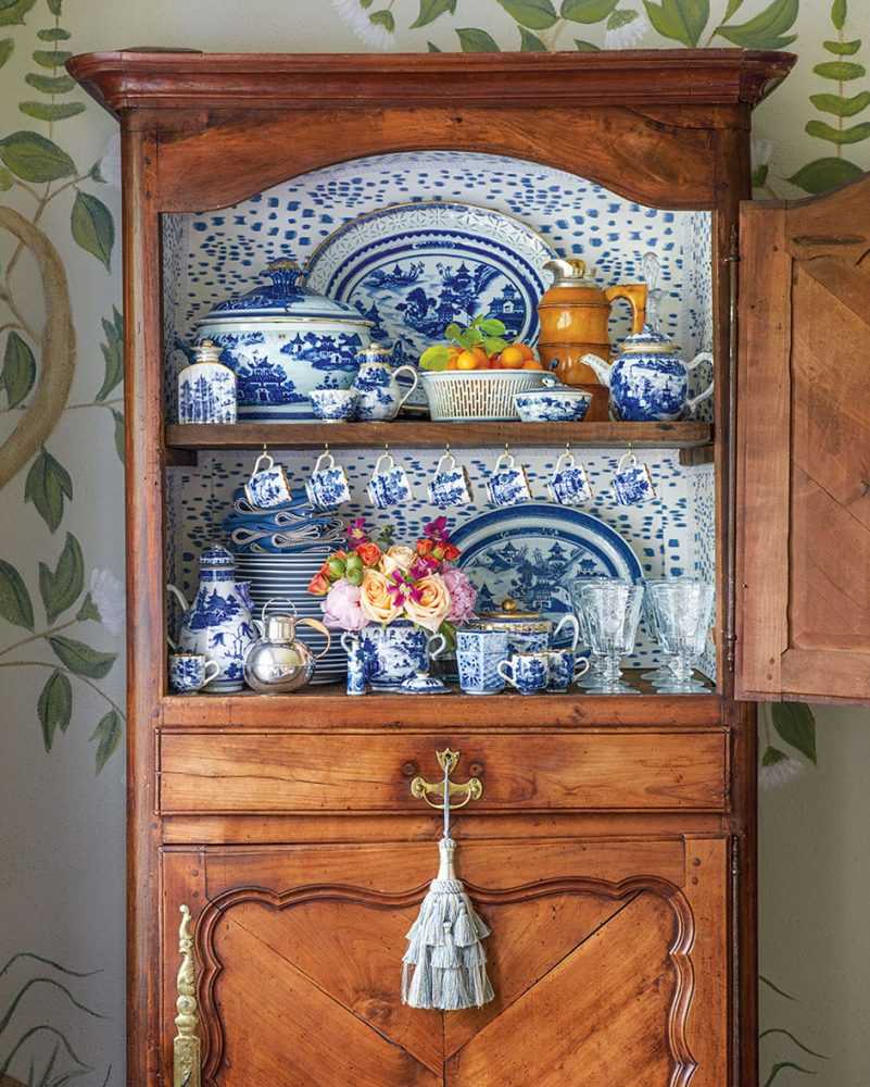 wood china cabinet, open to reveal the china inside the top half. Below, a large pale blue decorative tassel hangs from the drawer handle.
