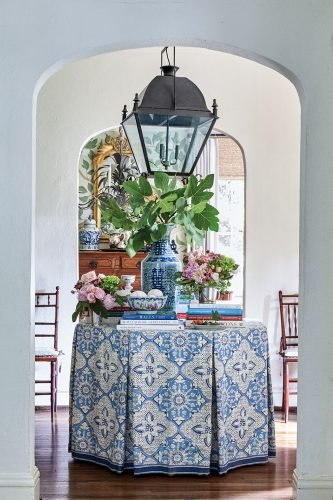 A round table in an entry is topped with a tailored blue-and-white table skirt, blue-and-white pottery, books, and floral arrangements.