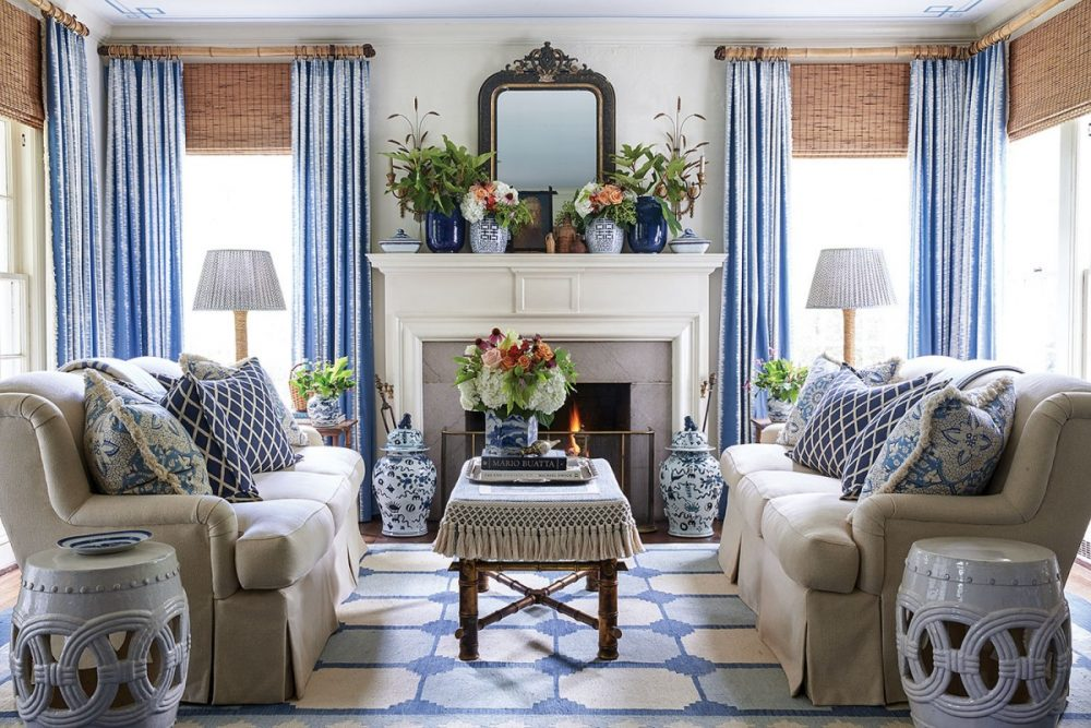 A symmetrical seating arrangement centered in front of a white painted mantel includes two facing sofas upholstered in a light neutral color, with blue-and-white throw pillows in two patterns--one diamond-shaped and modern, and the other floral and fringed. Pale blue floor-to-curtains, a blue and white rug, and an assortment of blue-and-white urns and vases throughout the room continue the theme