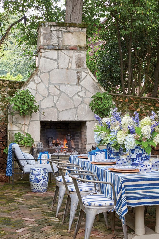 Another view of the outdoor table shows the Vietri blue polka dot glass tumblers and the metal dining chairs with blue-and-white striped seats and an outdoor stone fireplace with a roaring fire.
