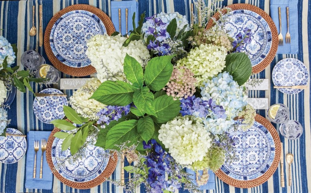Overhead view of table set with a blue-and-white striped tablecloth, light blue napkins, rattan chargers, and a large vase of blue and white hydrangeas