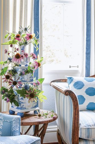 The flower arrangement sits on a side table in the bedrooms sitting area between a settee and a chair, both upholstered in various patterns of blue-and-white, including stripes, dots, and a botanical leaf print