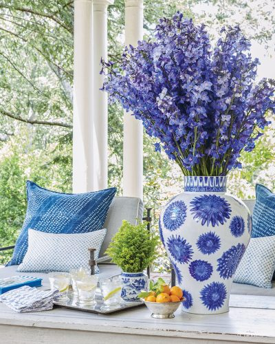 A large blue-and-white vase of blue flowers decorates a covered porch with ample seating