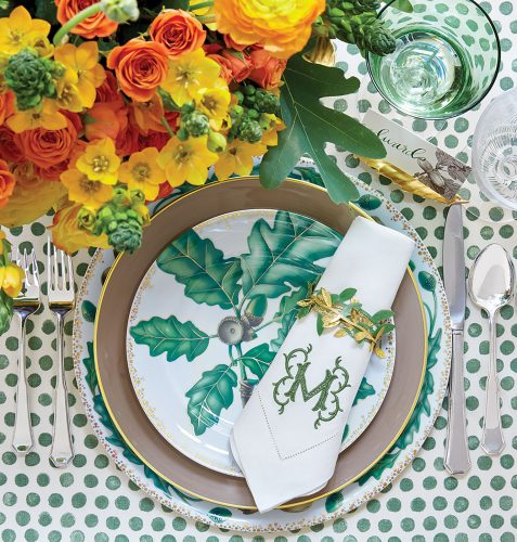 Fall table setting featuring green accents, including a leaf motif on the plates, the monogram on the napkin, and polka dots on the tablecloth. A flower arrangement of yellow and orange contrasts with the green, allowing all the colors to pop.