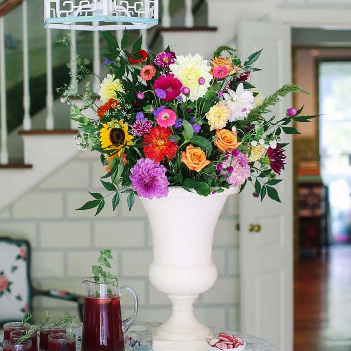 Large zinnia flower arrangement in a white urn