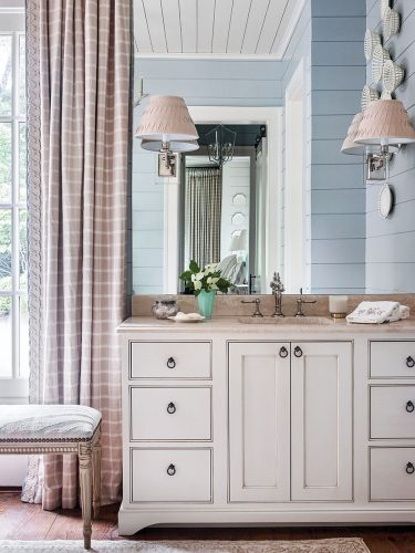 """Light blue paint distinguishes the shiplap walls of the master bath from the other rooms, while white and neutral gingham curtain panels and a soft white sink vanity with a light neutral stone countertop maintain consistency with the materials Francie Hargrove used throughout her """"chic mountain house"""" design theme."""