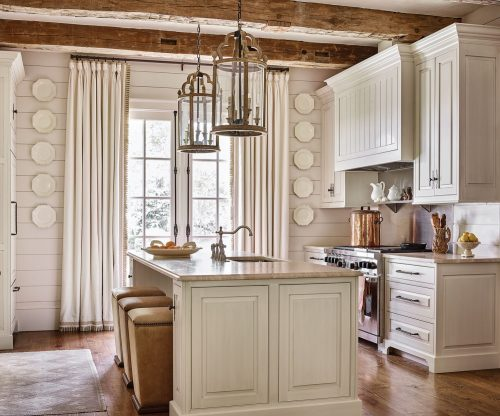 Francie Hargrove stuck with a white and neutral color palette in this kitchen, including a soft white painted finish for the cabinets and a light, neutral stone countertop. At the kitchen island, square barstools feature solid bases, simple lines, light leather upholstery, and a border of grommets just below the seat. Two large custom lanterns, designed by Francie Hargrove, hang above the island. Five white octagonal porcelain plates hang in a vertical line on either side of soft white curtains, flanking the French doors. A large antique copper pot sits on a stainless steel oven.