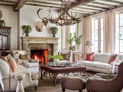 Other mountain house design ideas from this scene include a large chandelier made of deer antlers, a pair of sofas and side chairs upholstered in a soft white fabric, and throw pillows, including (on each sofa) a pair of pillows in strié coral velvet inset with a Greek key pattern, as well as (on each side chair) an leopard-print linen pillow. One tufted, curved accent chair with a matching ottoman is upholstered in a dark brown linen-type fabric. At the center of the seating area is a large square coffee table upholstered in a dark, rich fabric. A neutral patterned area rug grounds the seating area. Arrangements of simple cut greenery on the mantel, coffee table, and console add a punch of color. Swing-arm floor lamps and stacks of books invite one to sit and read by the fire. Soft white shiplap walls and curtains keep the room light and airy.