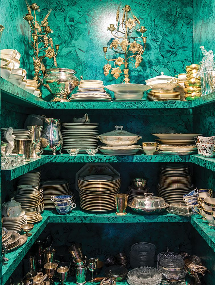 A china closet with four levels of shelves of three sides holds stacks of china, elegant gilt candelabras, and silver serving pieces. Bright teal walls and matching shelves feature a pattern that resembles marbling.