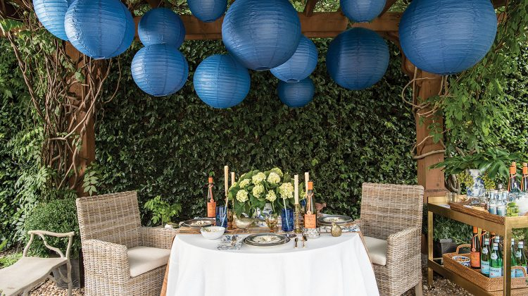 More than a dozen large, blue, spherical Chinese lanterns hang from a pergola above an outdoor party scene from the pages of Entertaining at Home by Ronda Carman. The scene also features a table with a white tablecloth and an arrangement of white hydrangeas. There are two rattan armchairs at the table. A bench sits to one side, and a stocked bar cart to the other. The background is lush with a thick wall of greenery.