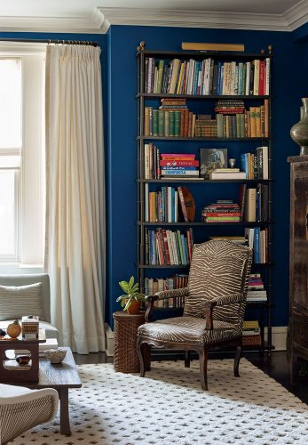 A zebra-print upholstered armchair punctuates the sitting area of a Tom Scheerer-designed room. Natural white, floor-to-ceiling curtain panels and a plush natural white rug, which features a raised pattern outlining diamond shapes, balances the deep blue paint on the walls. A tall, full set of bookshelves gives the room a lived-in look.