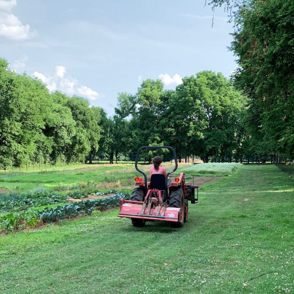 A farmer rides a tractor alongside a field of crops surrounded by trees at Gardens at Glen Leven