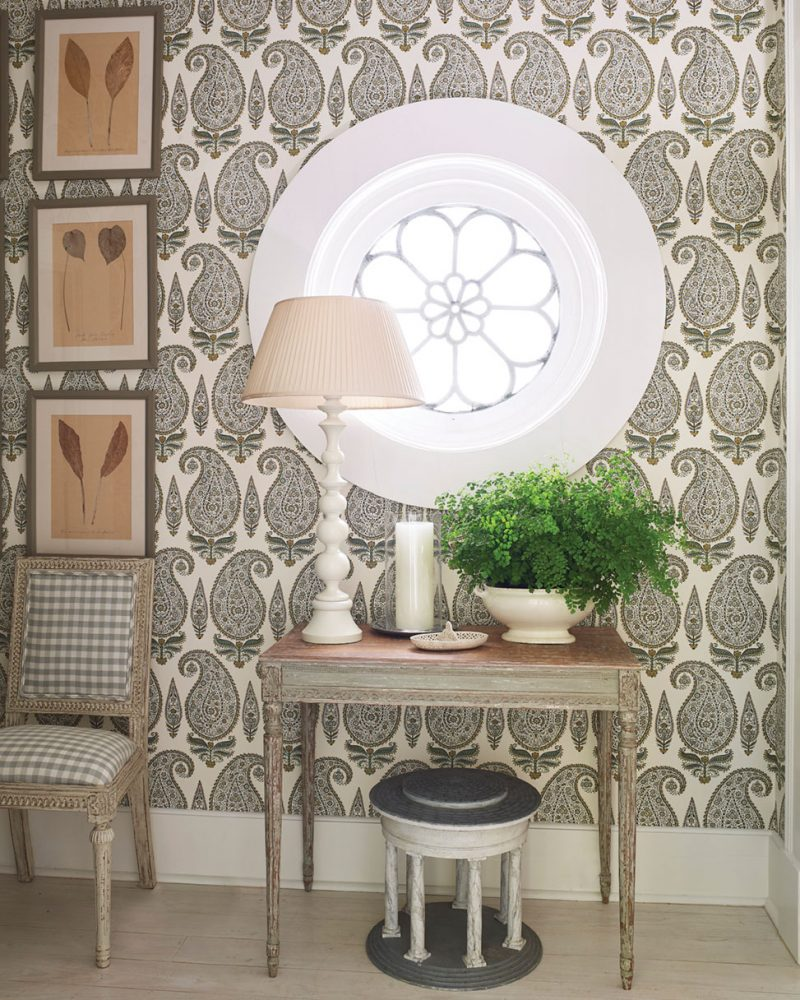 The Cathy Kincaid-designed room features an all-neutral palette, with a green fern adding a pop of color. A small table and lamp sit beneath a circular leaded window with a floral motif. A small chair is upholstered in a khaki and white check, contrasting with the paisley wallpaper. Above the chair, three leaf prints hang in a vertical column configuration.