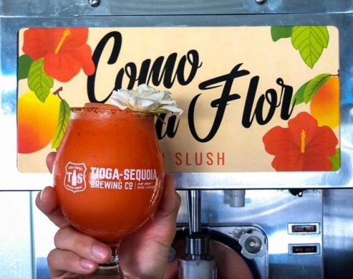 A hand holds a beer slushy in a tulip glass in front of a colorful sign reading Como la Flor