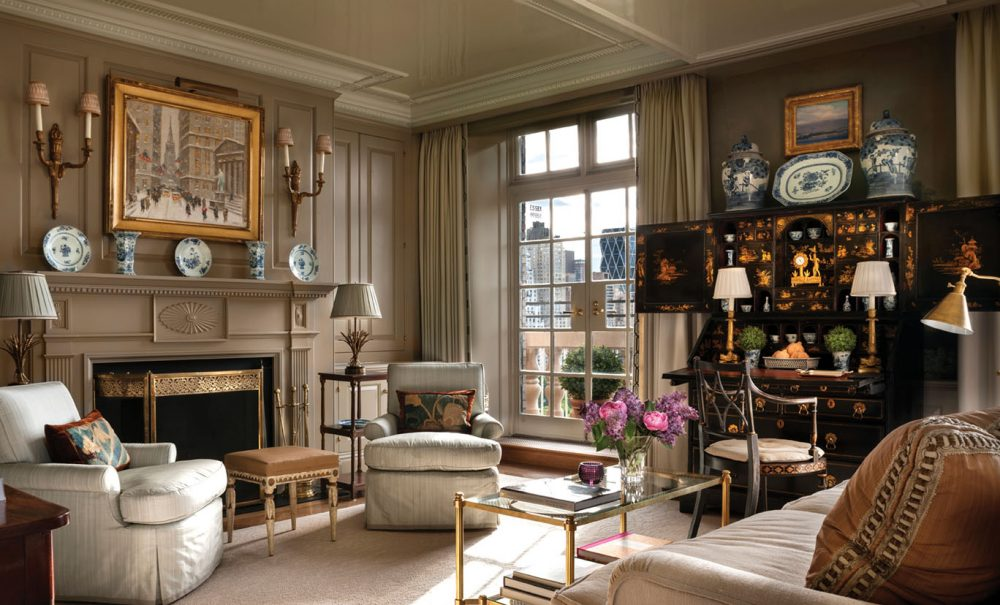 A fireplace surround with classic woodwork embellishments is painted the same neutral color as the wainscoting walls and curtain panels. Touches of blue-and-white, gold, and bronze, along with a colorful vase of pink and purple blooms, punctuate the serene space with color. A mullioned window offers a view of the city.