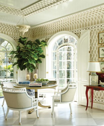 The room features a tray ceiling, arched french doors, a table and three chairs, a wood floor painted in a light gray and white diamond pattern, and a small indoor tree with large green leaves in a blue-and-white porcelain pot.