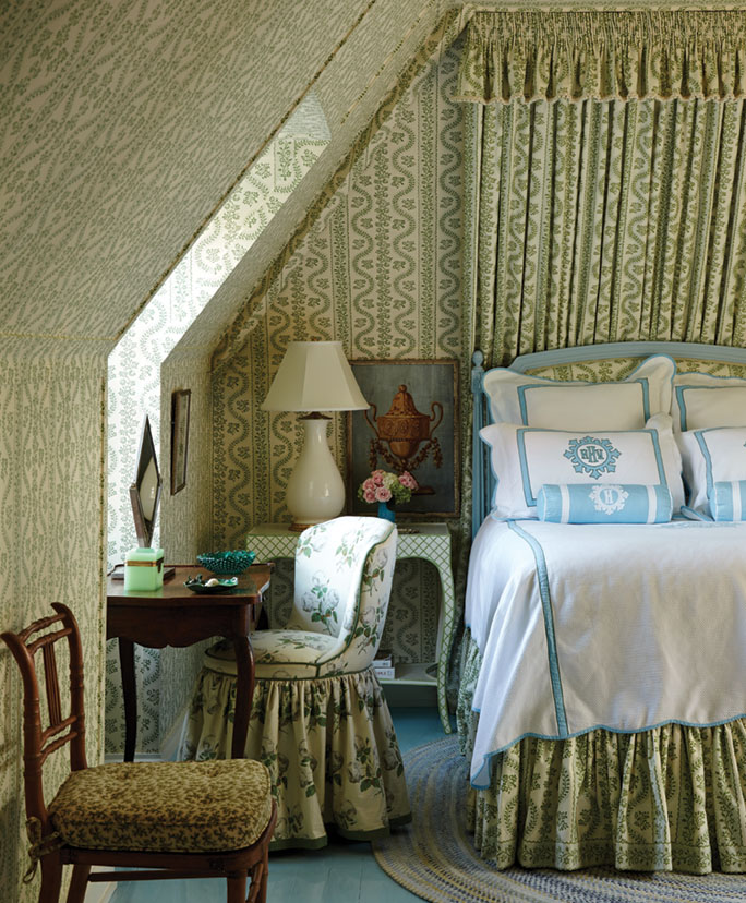 Behind the blue painted bedframe, a gathered, floor-to-ceiling fabric panel with valance displays the same botanical, sage green print as the wallpaper that envelops the space. The bed skirt also features the 'Dolly' Sister Parish print, while a skirted upholstered chair at the small antique desk by the window features a complementary floral pattern. Fresh white bedding is trimmed in a robin's egg blue.