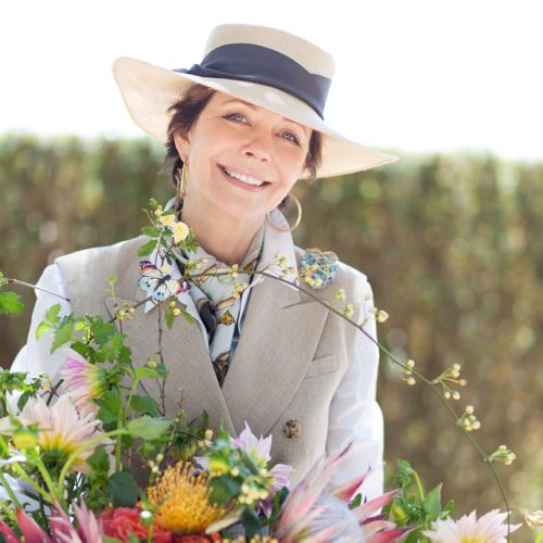 portrait of Frances Schultz in a wide brimmed hat, with a large bouquet of wild flowers