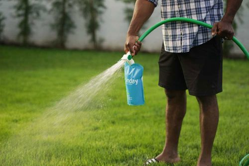 demonstration of a man using a hose with sprayer attachment to apply Sunday lawn fertilizers. Photo via Sunday