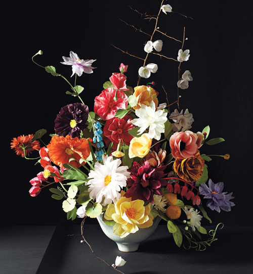 Colorful, realistic-looking paper flowers arranged in a compote vase against a dark background.