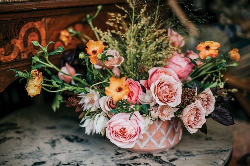 Finished floral arrangement demonstrated by Kelly Marie Thompson. Materials: Pieris japonica, Plum tree foliage, Bridal veil grass , Millet grass, Explosion grass, 'Blushing Bride' protea', Prairie Sunset' roses, 'Romantic Antike' roses, 'Koko Loko' roses, 'Butterfly' ranunculus