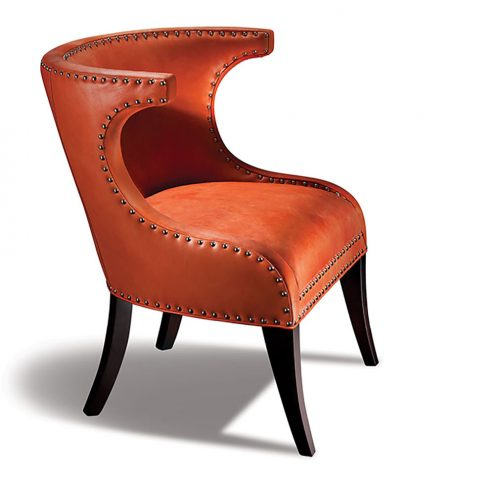 """chair featuring orange """"chrysanthemum-colored' leather upholstery and dramatic curving lines accentuated by grommet outline"""