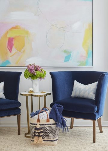 Two deep blue wing chairs flank a small side table with a brass base and stone top. On the wall hangs a very large, airy abstract painting, with a primarily white (or very pale) background and punches of bright yellow, pink, aqua and green.