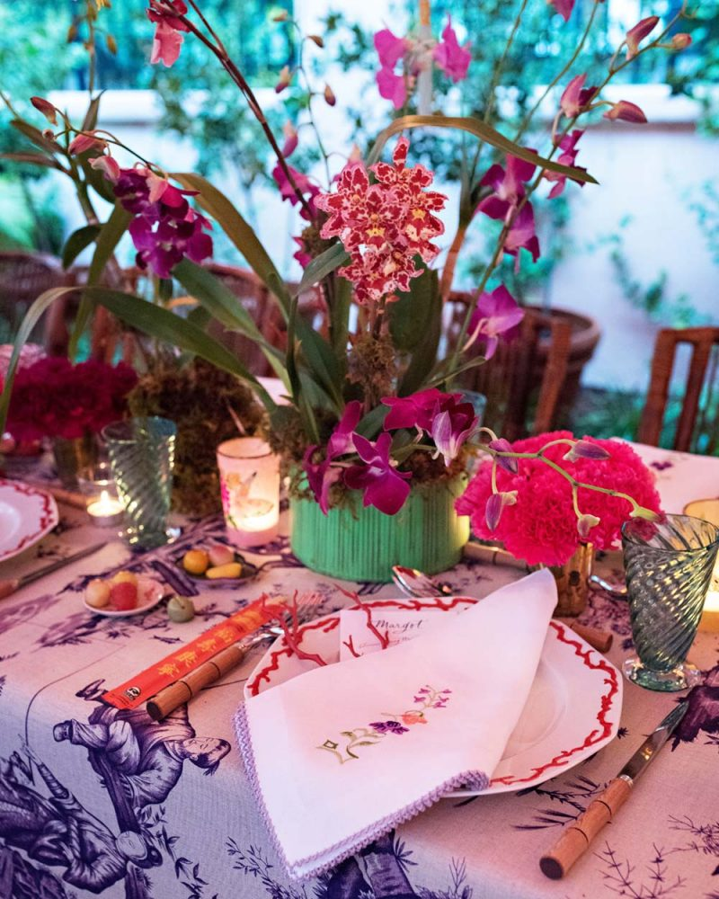 Table set for a dinner part with a blue-and-white chinoiserie table cloth and potted orchids.