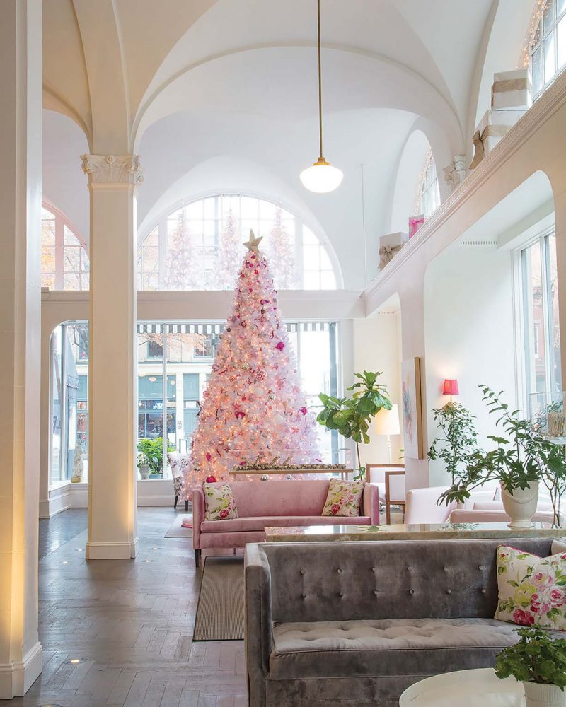 A white Christmas tree decorated with silver and red ornaments and white lights in Quirk Hotel in Richmond, Virginia. The light and airy lobby features a vaulted ceiling.