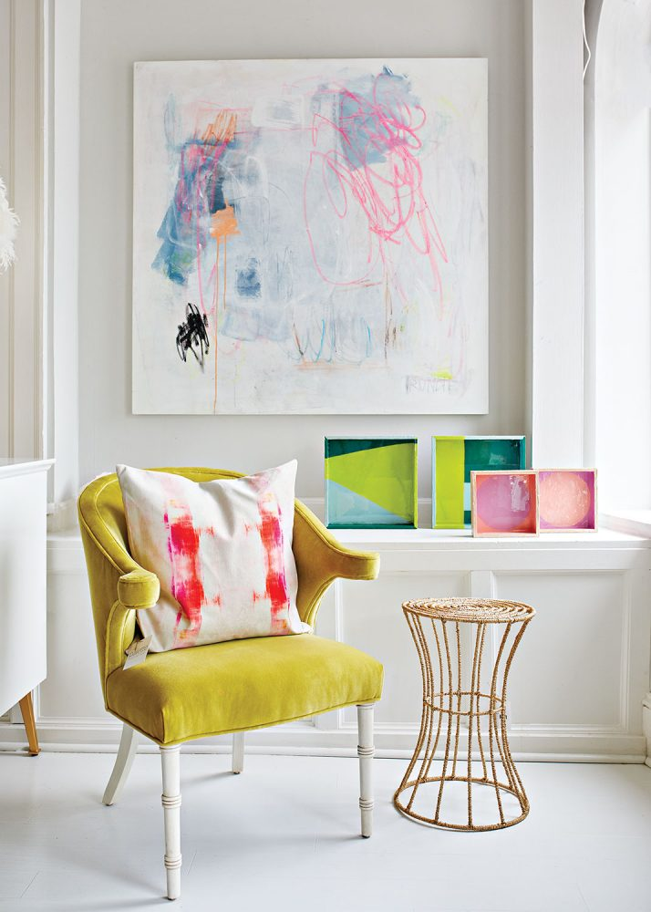 Best shopping in Richmond, Virginia: Palette Paint and Home. Photo of an avocado green velvet armchair sits next to a modern metal-base round occasional table. Bright and colorful abstract art punctuates the white room.