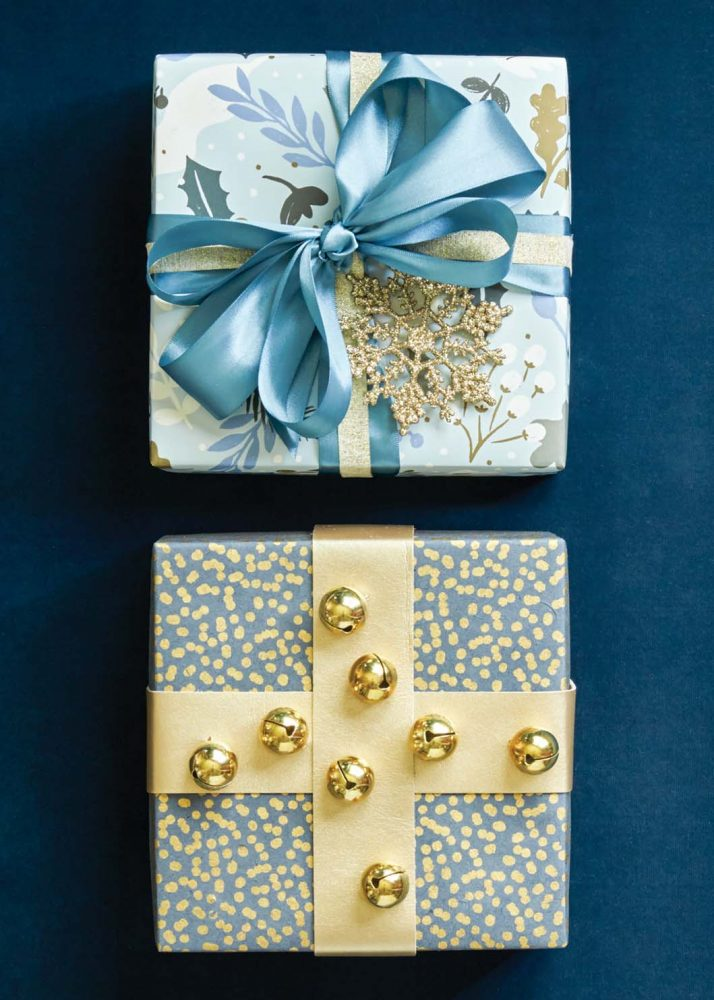Holiday gift wrap ideas with blue and gold, and jingle bell balls attached to criss-crossed gold ribbon