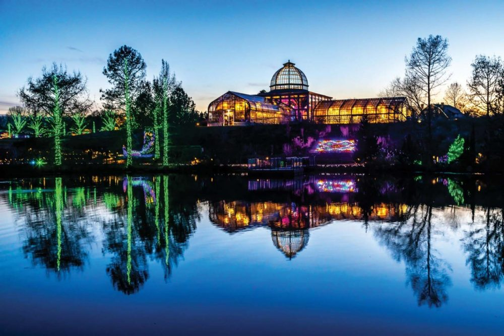 A must for holiday sightseeing in Richmond: An evening view of the massive glass conservatory, with the grounds of Lewis Ginter Botanical Garden decorated in holiday lights