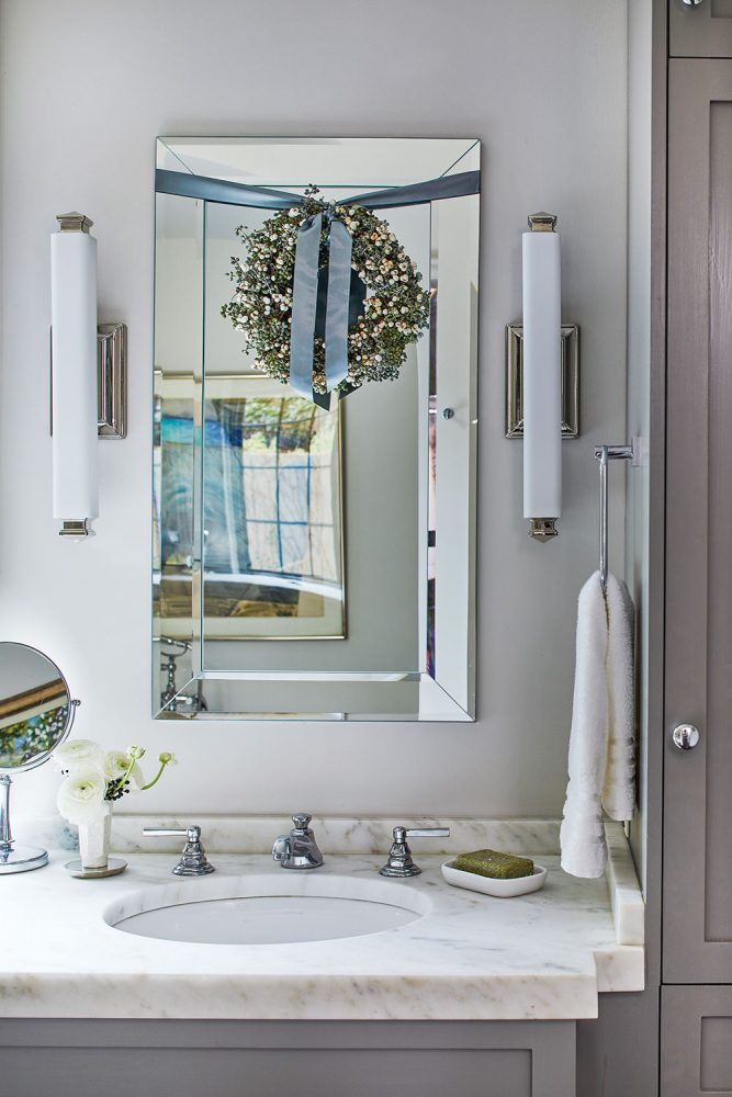 A wreath hangs from the mirror in the sleek white and gray master bath with marble counters