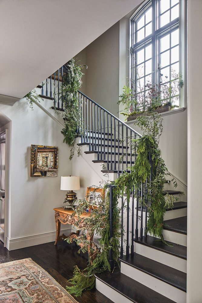 stair rail decked in greenery for holiday home tour