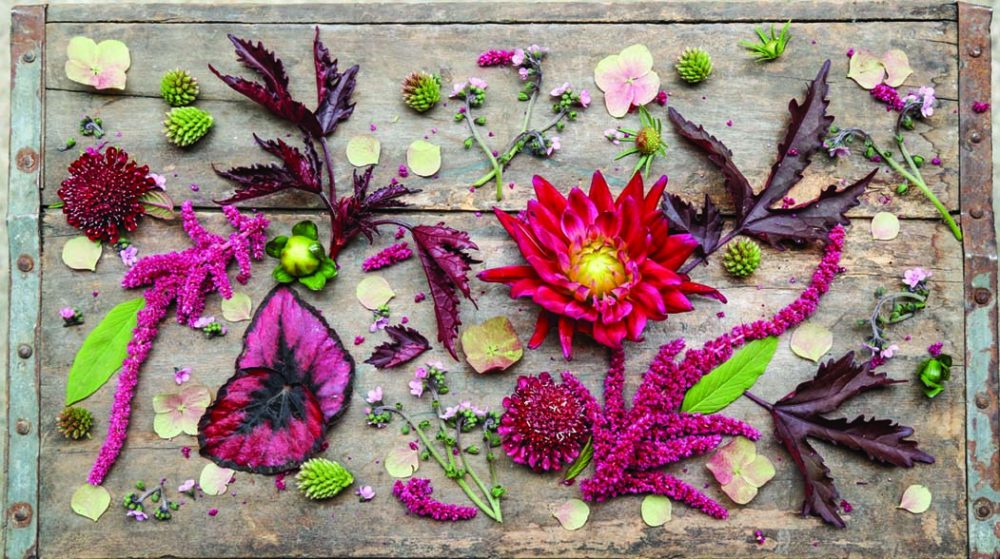 Flowers and leaves artfully arranged on a rustic wooden table at Strawberry Fields, one of designer Amanda Nisbet's picks for best shopping in Richmond, Virginia