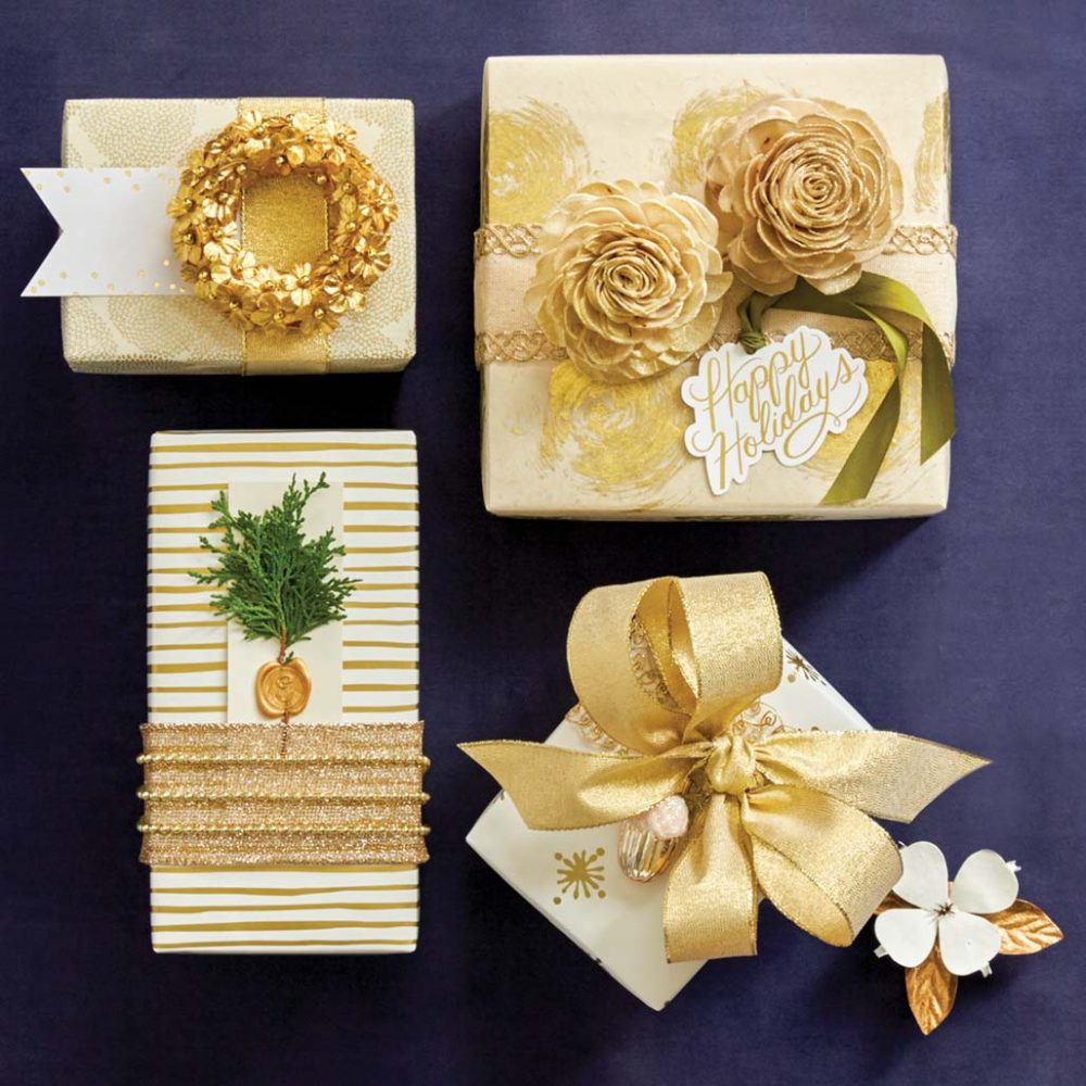 Presents wrapped in gold-and-cream colored paper. Adornments include a small golden wreath, golden rosettes, a small golden acorn ornatment, and a spring of greenery adhered with a wax seal